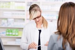 Female pharmacist reads a medicine prescription Stock Photos