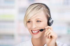 friendly female pharmacist using headsets - stock photo