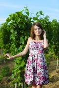 Elegant young woman outdoor portrait lean on wall covered in vines Stock Photos