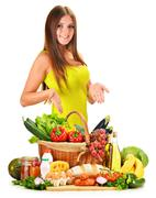 Young woman with assorted grocery products isolated on white background Stock Photos