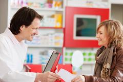 pharmacist receiving prescription paper from customer - stock photo