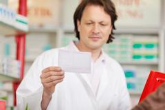 pharmacist reading prescription - stock photo