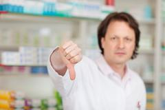 pharmacist showing thumbs down - stock photo
