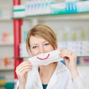 pharmacist with mask smiling - stock photo