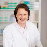 male pharmacist smiling in pharmacy - stock photo