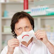 pharmacist holding mask with sad smiley - stock photo