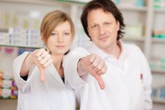pharmacists showing thumbs down - stock photo
