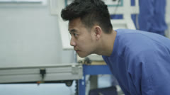 Mixed ethnicity team of machine operators in a factory - stock footage