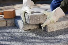 construction worker paving the brick road - stock photo