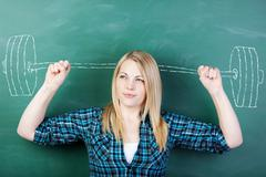 student clenching fists with barbell drawn on chalkboard - stock photo