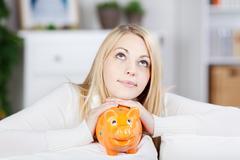 Young thinking woman holding orange piggy bank Stock Photos