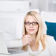 Young woman sit on the sofa with laptop Stock Photos