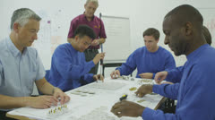 Happy male factory staff of mixed ethnicity assembling electrical fittings Stock Footage