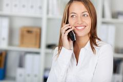 Businesswoman using cordless phone while looking away Stock Photos