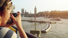 Tourist photographer filming London Eye Big Ben Sightseeings at sunset Stock Footage