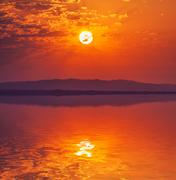 vibrant rising sun at dawn over water - stock photo