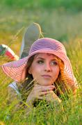 Teen girl lying in meadow grass Stock Photos