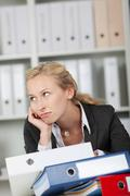 bored businesswoman with binders - stock photo