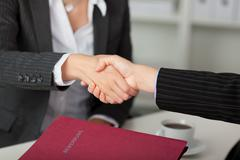 Businesswoman shaking hands at desk Stock Photos