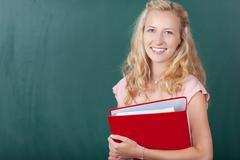 teacher holding binder against chalkboard - stock photo