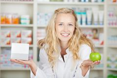 female pharmacist holding pill box and an apple - stock photo