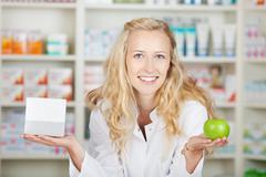 Female pharmacist holding pill box and an apple Stock Photos