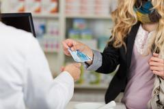 Pharmacist receiving money from woman for medicines Stock Photos