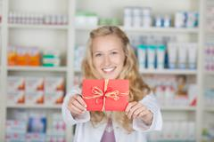 female pharmacist with bonus coupon card gift - stock photo