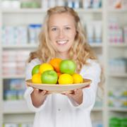 female pharmacist holding plate of fruits - stock photo
