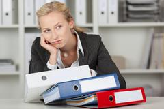 bored blond businesswoman with binders - stock photo