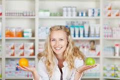 pharmacist with apple and orange - stock photo