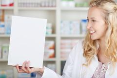 Female pharmacist holding blank paper Stock Photos