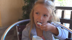 Child Eating Cream in a Cup at Restaurant, Little Girl Tasting Junket at Dinner Stock Footage