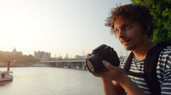Tourist travel photographer photographing London city at sunset Stock Footage