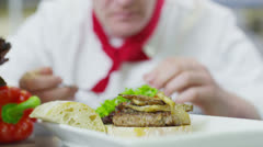 Stock Video Footage of Delicious gourmet burger is being given the finishing touches by the chef