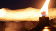 Tiki torch close-up series, with unfocused party lights behind Stock Footage