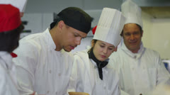 Happy team of chefs in a commercial kitchen, head chef tastes and gives approval Stock Footage