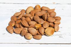 Almonds unpeeled nuts on white wooden background Stock Photos