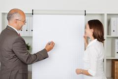 Stock Photo of businessman writing on flipchart