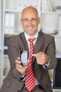 mature businessman pointing at cell phone - stock photo