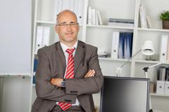 Successful businessman with folded arms Stock Photos