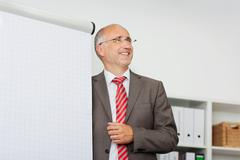 Smiling businessman presenting at flipchart Stock Photos