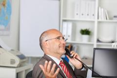 gesturing businessman using telephone - stock photo