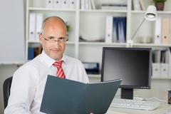 confident mature businessman with file at desk - stock photo