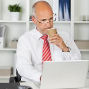 businessman using laptop while drinking coffee in disposable cup - stock photo
