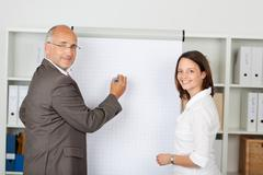 Businessman with female coworker standing near flipchart Stock Photos