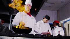 Professional chef in a commercial kitchen cooking flambe style. - stock footage