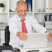happy employee holding his laptop - stock photo
