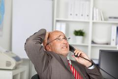Desperate businessman using telephone Stock Photos