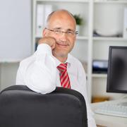 confident businessman rest on chin - stock photo